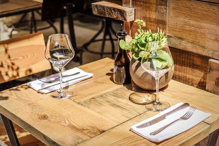 テーブルでワインのグラスとオープンエアのレストラン。