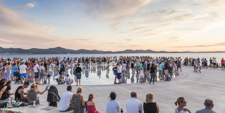 ZADAR, CROATIA - 11 JULY,2017: People at sunset beside Adriatic sea on circular solar panel installation Greeting to the Sun by architect Nicola Basic in Zadar, Croatia.