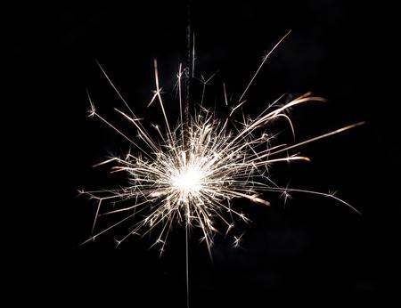 Burning sparkler on a dark or black background.