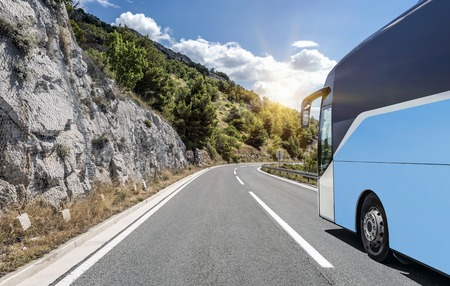 Tourist bus rushes along the country high-speed highway against the background of a mountain landscape. Banco de Imagens