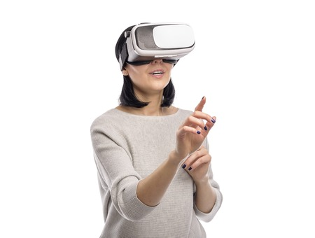 Young woman in a virtual reality helmet on a white.