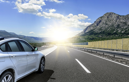 A white car rushing along a high-speed highway in the sun.
