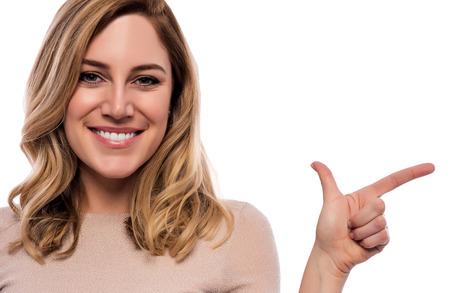 Attractive blonde points a finger at the empty space. Foto de archivo