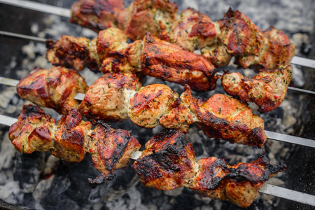 Barbecue or shish kebab is fried on the grill. Stock Photo