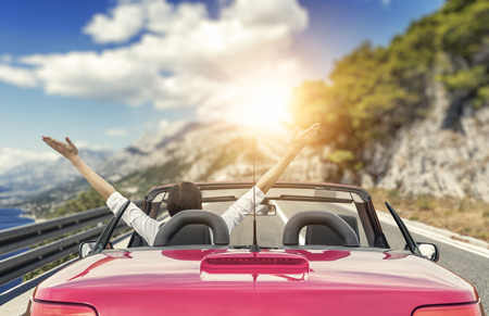 Young woman in a car on the road to the sea against a backdrop of beautiful mountains on a sunny day. Stock Photo
