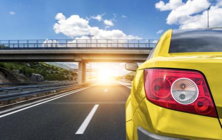 Yellow car rushing along a high-speed highway.