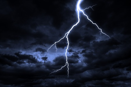 A lightning strike on a cloudy dramatic stormy sky. Stock Photo