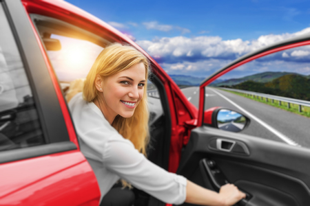 Beautiful blonde girl driving a car on the highway. Invitation to travel. Car rental or vacation.