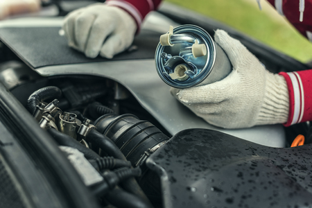 An auto mechanic replaces a cars fuel filter.