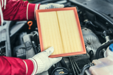 The auto mechanic replaces the cars air filter.