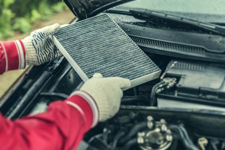 El mecánico de automóviles reemplaza el filtro interior del automóvil. Foto de archivo