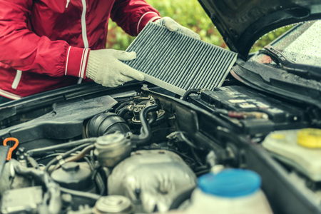 The auto mechanic replaces the cars interior filter.