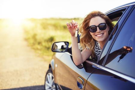 Une jolie femme dans une voiture tient une clé de voiture dans sa main. Banque d'images