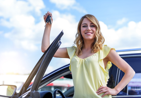 An attractive woman standing near the car holds a car key in her hand.
