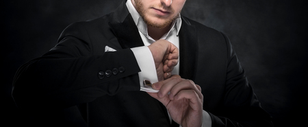 Elegant young fashion man looking at his cufflinks over dark background.