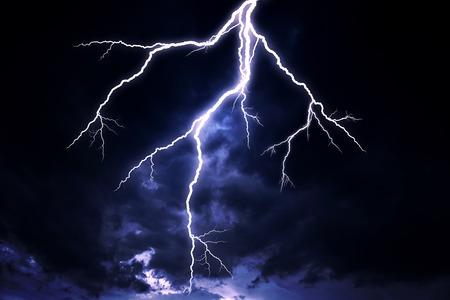 A lightning strike on a cloudy dramatic stormy sky. Stock Photo