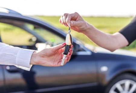 One woman hands over another car key. Rent or purchase of auto. Reklamní fotografie