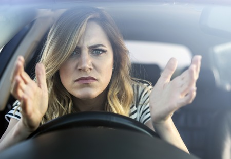 Angry woman driving a car. Imagens