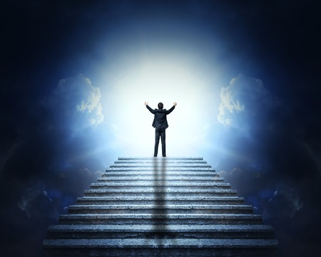A man in a suit with arms outstretched on a stone staircase to the clouds and light. Stairway to Heaven. Reklamní fotografie