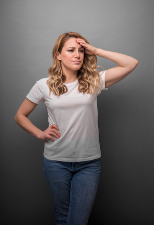 A woman thinks holding her head or has a headache.