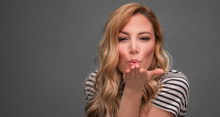 Portrait of pretty blonde girl blowing air kiss on grey background.