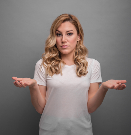 Young woman raises her hands up showing surprise or denial. Stock Photo