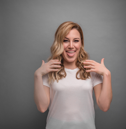 Woman shows on herself posing on gray background. Stock Photo