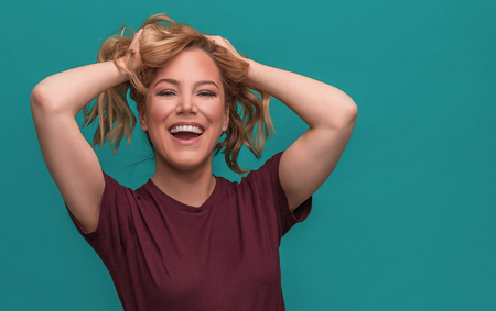 Attractive blonde rejoices with her hands behind her head, relaxing and smiling. Stock Photo - 120895669