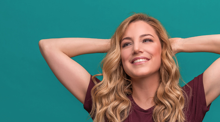 Attractive blonde rejoices with her hands behind her head, relaxing and smiling. Beautiful young woman on blue background.