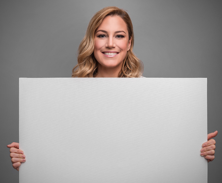 Attractive blonde holds white blank empty poster for your text or image on a gray background.