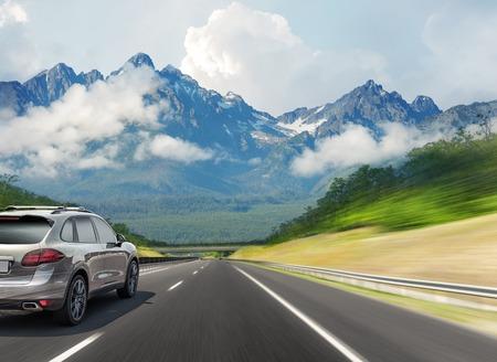 Das Auto fährt schnell auf der Autobahn vor der Kulisse einer Bergkette. Standard-Bild