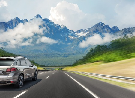 The car drives fast on the highway against the backdrop of a mountain range. Reklamní fotografie