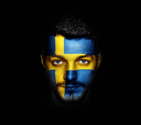 Flag of Sweden painted on a face of a man. Stock Photo