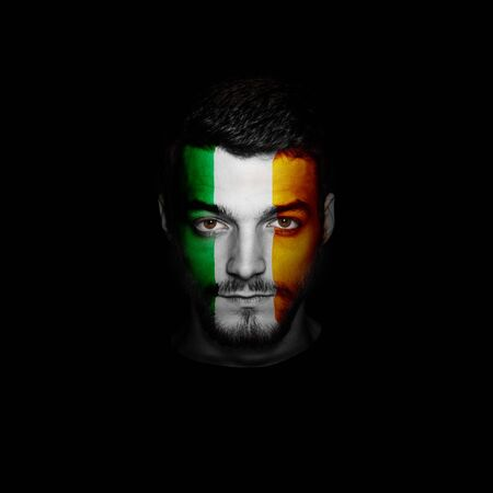 Flag of Ireland painted on a face of a man.