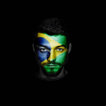 Flag of Brazil painted on a face of a man.