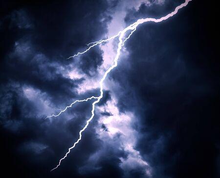 Uderzenie pioruna na zachmurzonym, ciemnym niebie.