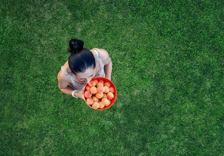 Young woman with a tray of fruit on a background of green grass.