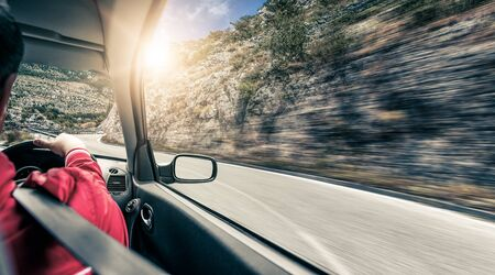 The driver rushes along the mountain road by car. View from inside the car.