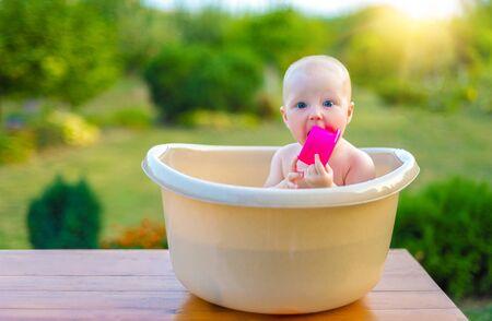 De baby baadt op een zomeravond in een bad in de tuin.