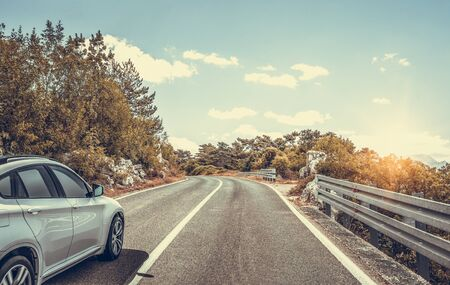 Car moves on the road among the mountains and forests.