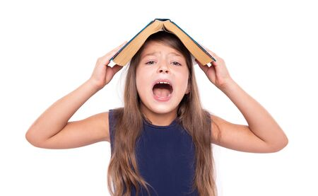 Kleines Mädchen mit einem offenen Buch auf dem Kopf ist wütend.
