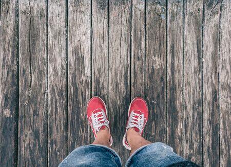 Feet in sneakers on a wooden floor. Stockfoto