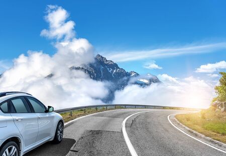 Car moves on the road among the mountains and forests. Stockfoto