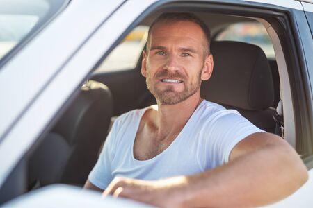 A man driving a white car.