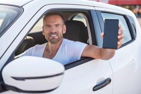 An attractive man in a car shows a smartphone.