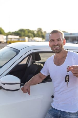 A male driver stands near a car with a key in his hand and smiles.