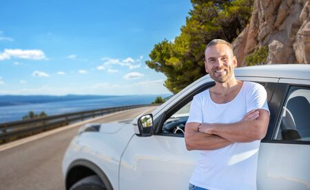A young man stands near a car on a background of the sea coast. Stockfoto