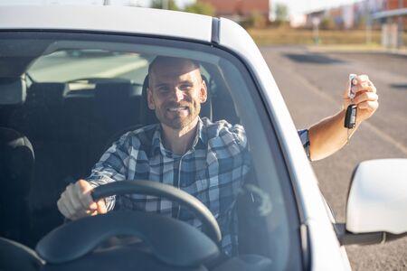 A man in a white car shows a key.