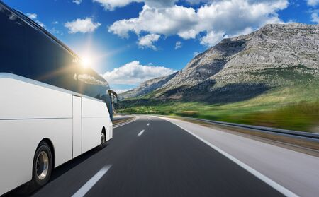 Un autobús blanco sin marca se apresura a lo largo de una carretera. Foto de archivo