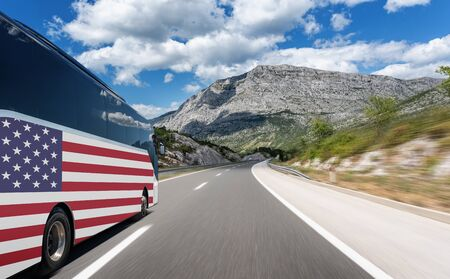 Bus with the flag of the United States of America rushes along the highway. Trip to usa - concept.